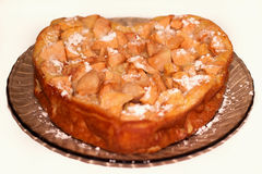 Apple pie in the form of heart. Poured by icing sugar Royalty Free Stock Photos