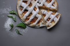 Apple pie on grey background. Dessert. Homemade cake. Autumn flatlay. Homemade piece of cake with mint and sugar powder. Apple pie on grey background. Homemade royalty free stock photography