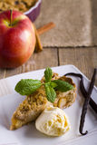 Apple pie with ice cream, decorated with vanilla, mint and cinnamon on wooden background. A delicious piece of cake with ice. Royalty Free Stock Images