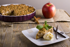 Apple pie with ice cream, decorated with vanilla, mint and cinnamon on wooden background. A delicious piece of cake with ice. Stock Image