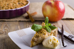 Apple pie with ice cream, decorated with vanilla, mint and cinnamon on wooden background. A delicious piece of cake with ice. Stock Images