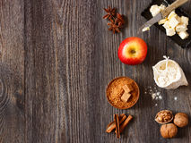 Apple pie. Ingredients for apple pie cooking. Fresh red apple, butter, flour, brown sugar, nuts and spices on a rustic wooden background Stock Photos