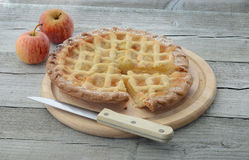 Apple pie with knife and apples Royalty Free Stock Image