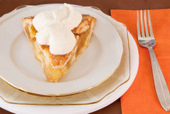 Apple pie a la mode. Apple pie with scoops of vanilla ice cream on top. A la mode style. Triple plates with a brown background, orange napkin and a fork Royalty Free Stock Photo