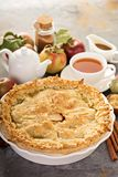 Apple pie with leaves cut outs. Homemade apple pie with leaves cut outs served with tea and caramel sauce royalty free stock photography