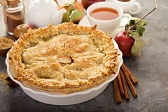 Apple pie with leaves cut outs. Homemade apple pie with leaves cut outs served with tea and caramel sauce stock image