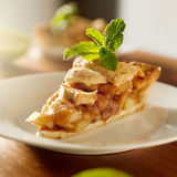 Apple pie with mint garnish. Photo of a piece of apple pie on a plate with mint garnish shot with selective focus stock photo