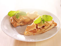Apple pie with mint garnish in warm sunlight Stock Photos