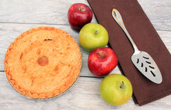 Apple pie next to apples and pie cutter Stock Photo
