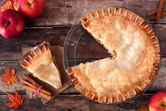 Apple pie, overhead scene with cut slice on rustic wood Stock Photography