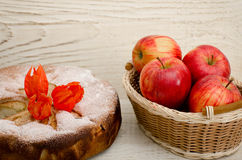 Apple pie, Physalis flowers and ripe apples on a light wooden table Stock Photo