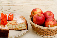 Apple pie, Physalis flowers and ripe apples on a light wooden table Royalty Free Stock Image