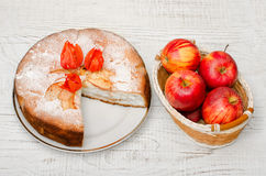 Apple pie, Physalis flowers and ripe apples on a light wooden table, top view Royalty Free Stock Photo