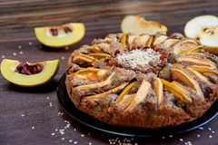 Apple pie with quince, poppy seeds, raisins and sesame on the dark plate decorated with sliced fresh apples and quince. On wooden brown table. Side view Royalty Free Stock Photos