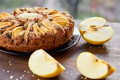 Apple pie with quince, poppy seeds, raisins and sesame on the dark plate decorated with sliced fresh apples on wooden brown table stock photo