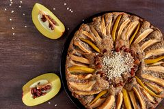 Apple pie with quince, poppy seeds, raisins and sesame on the dark plate. Tart decorated with sliced fresh quince. On wooden brown table. Top view Stock Photos