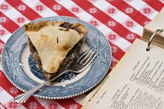 Apple Pie and Recipe. Slice of pie and the recipe book it came from on vntage blue plate with vintage recipe book Royalty Free Stock Images