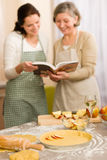 Apple pie recipe two women looking cookbook. Apple pie recipe two women looking in cookbook happy baking Stock Image