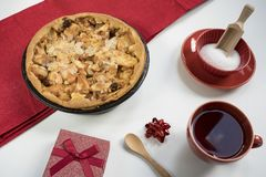 Homemade apple pie with present, cup of tea and sugar. royalty free stock image