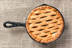 Apple Pie in Skillet. High angle view of a skillet baked apple pie n a burlap table cloth Royalty Free Stock Photos