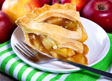 Apple Pie Slice. Plate of apple pie with fresh apples in the background - Horizontal