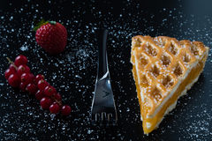 Apple pie slice on black table with currant and strawberry. Fresh apple pie slice on black table with currant and strawberry Stock Images