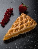 Apple pie slice on black table with currant and strawberry. Fresh apple pie slice on black table with currant and strawberry Royalty Free Stock Photography