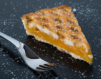 Apple pie slice on black table with fork. Fresh apple pie slice on black table with fork and sugar Stock Images