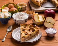 Apple pie slice with ingredients. Fresh baked apple pie slice on rustic table setting with ingredients Royalty Free Stock Photo