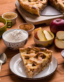 Apple pie slice with ingredients. Fresh baked apple pie slice on rustic table setting with ingredients Royalty Free Stock Images