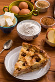 Apple pie slice with ingredients. Fresh baked apple pie slice on rustic table setting with ingredients Stock Images