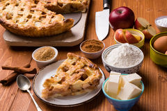 Apple pie slice with ingredients. Fresh baked apple pie slice on rustic table setting with ingredients Stock Photos