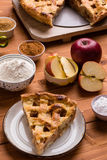 Apple pie slice with ingredients. Fresh baked apple pie slice on rustic table setting with ingredients Royalty Free Stock Photography