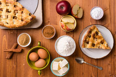 Apple pie slice with ingredients. Fresh baked apple pie slice on rustic table setting with ingredients Stock Photography