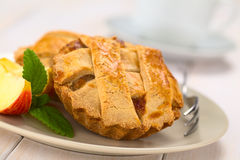 Apple Pie. Small round apple pie with lattice crust with pastry fork, mint leaf and apple slice on a plate, cup in the back  (Selective Focus, Focus one third Stock Photos