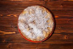 Apple pie sprinkled with powdered sugar on the background of a dark board. Apple pie sprinkled with powdered sugar on the background of dark board royalty free stock photography