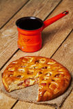 Apple pie and turkish coffee pot. Piece of apple pie on sackcloth and metal turkish coffee pot on planked wooden table Stock Images