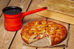 Apple pie and turkish coffee pot. Piece of apple pie on sackcloth, old book and metal turkish coffee pot on planked wooden table Royalty Free Stock Image