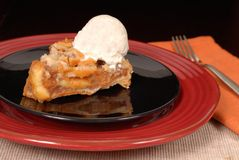 Apple pie with vanilla ice cream. Apple pie with vanilla bean ice cream on black plate Royalty Free Stock Photos