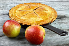 Apple pie. Warm homemade apple pie on skillet with two apples on gray wooden surface Royalty Free Stock Photography