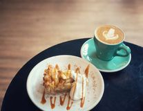Apple pie and whipping cream and latte art coffee in green cup on black table in coffee shop Stock Photo