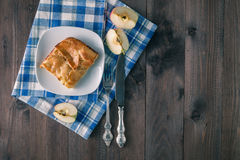 Apple pie on the white plate on wooden table Royalty Free Stock Photography