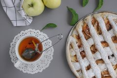 Apple pie with white towel on grey background. Dessert. Homemade cake with black tea and sieve. Autumn flatlay. Autumn homemade pi. Apple pie with white towel on stock photos