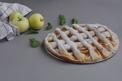 Apple pie with white towel on grey background. Dessert. Homemade cake with black tea and sieve. Autumn flatlay. Autumn homemade pi. Apple pie with white towel on stock image