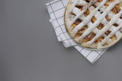 Apple pie with white towel on grey background. Dessert. Homemade cake with black tea and sieve. Autumn flatlay. Autumn homemade pi. Apple pie with white towel on stock photo