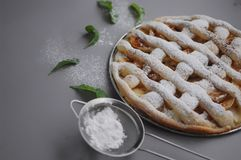 Apple pie with white towel on grey background. Dessert. Homemade cake with black tea and sieve. Autumn flatlay. Autumn homemade pi. Apple pie with white towel on stock images