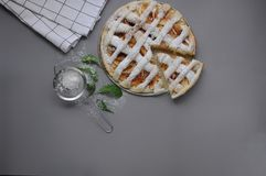 Apple pie with white towel on grey background. Dessert. Homemade cake with black tea and sieve. Autumn flatlay. Autumn homemade pi. Apple pie with white towel on royalty free stock photo