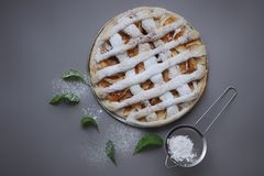 Apple pie with white towel on grey background. Dessert. Homemade cake with black tea and sieve. Autumn flatlay. Autumn homemade pi. Apple pie with white towel on royalty free stock image