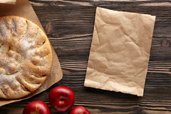 Apple pie. Apple pie on a wooden rustic table. Top view.  Piece kraft paper empty space for text Royalty Free Stock Photo