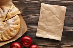 Apple pie. Apple pie on a wooden rustic table. Top view.  Piece kraft paper empty space for text Stock Photos